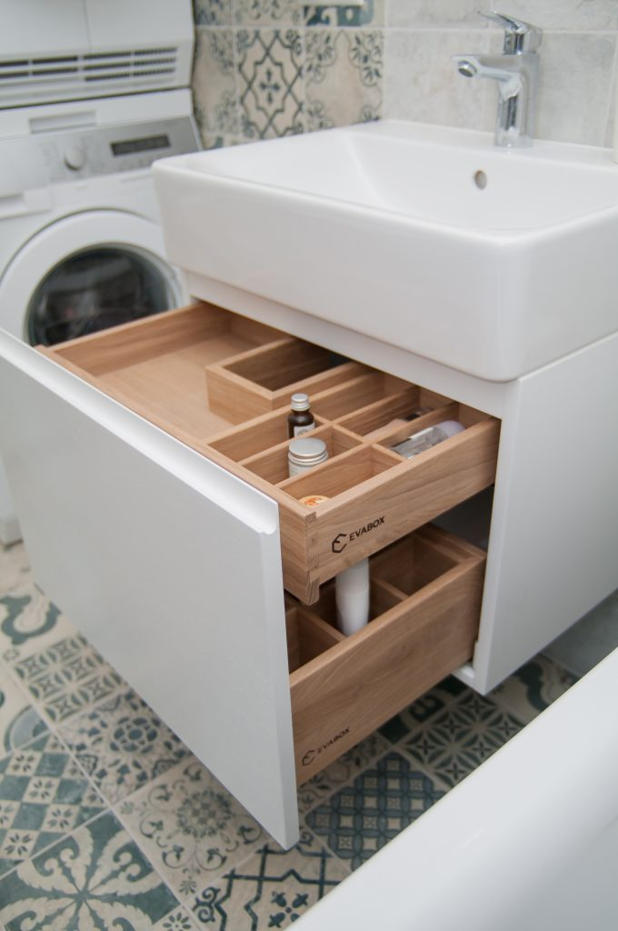 Wooden drawer in the bathroom under the sink with an insert